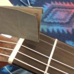 Gently sanding out burrs in the guitar nut