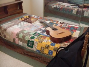 Rental 'beater guitar' placed across scrap quilt I made for Ma & Dad ~ 1983